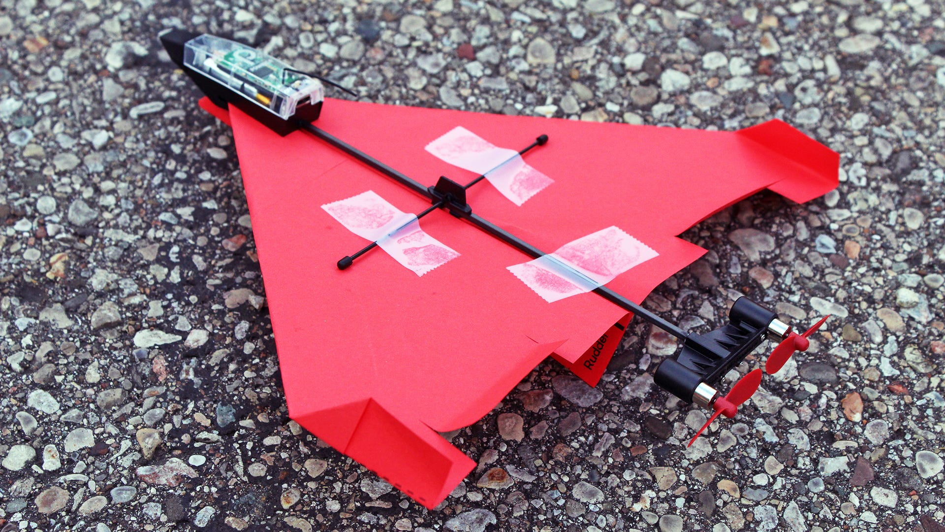 A paper airplane tethered to an RC airplane-like drone.