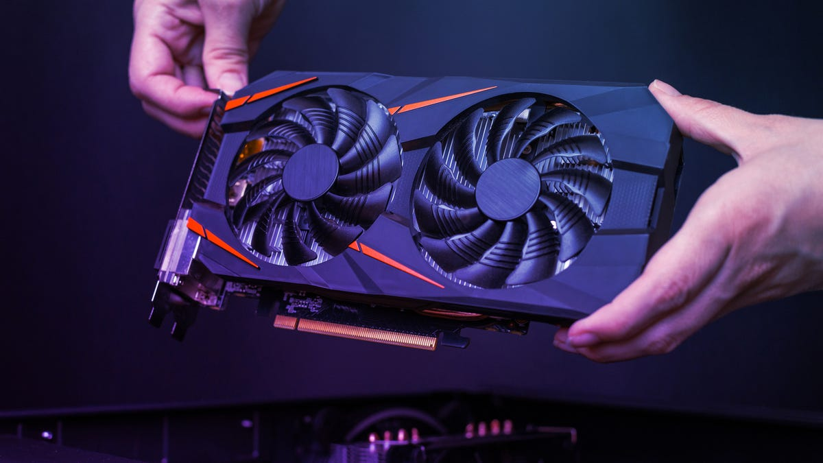 Hands holding a graphics card against a dark background