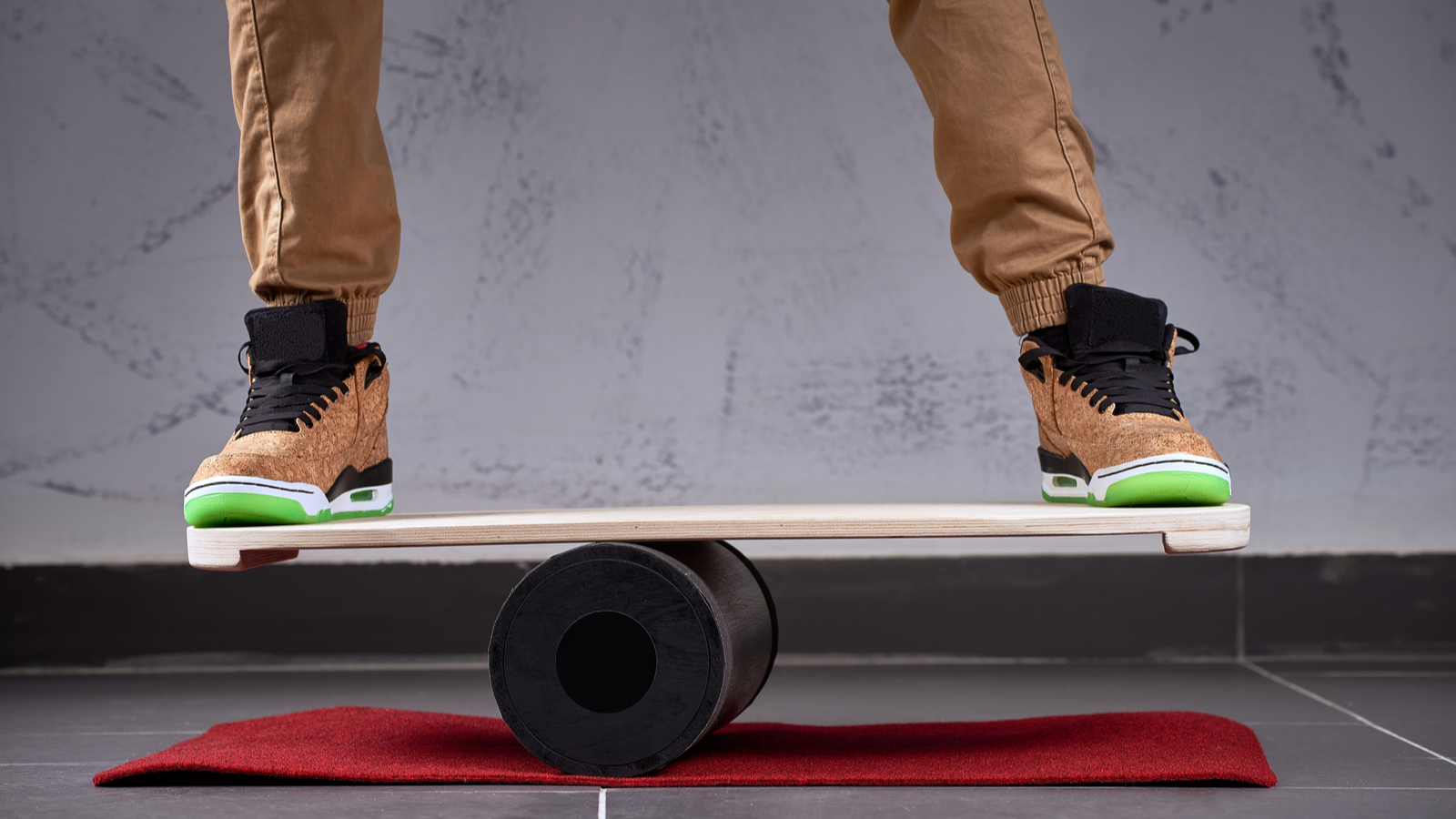 Oval wooden deck for balance board, solid plastic roller for balance board, person with skater shoes standing and balancing on deck