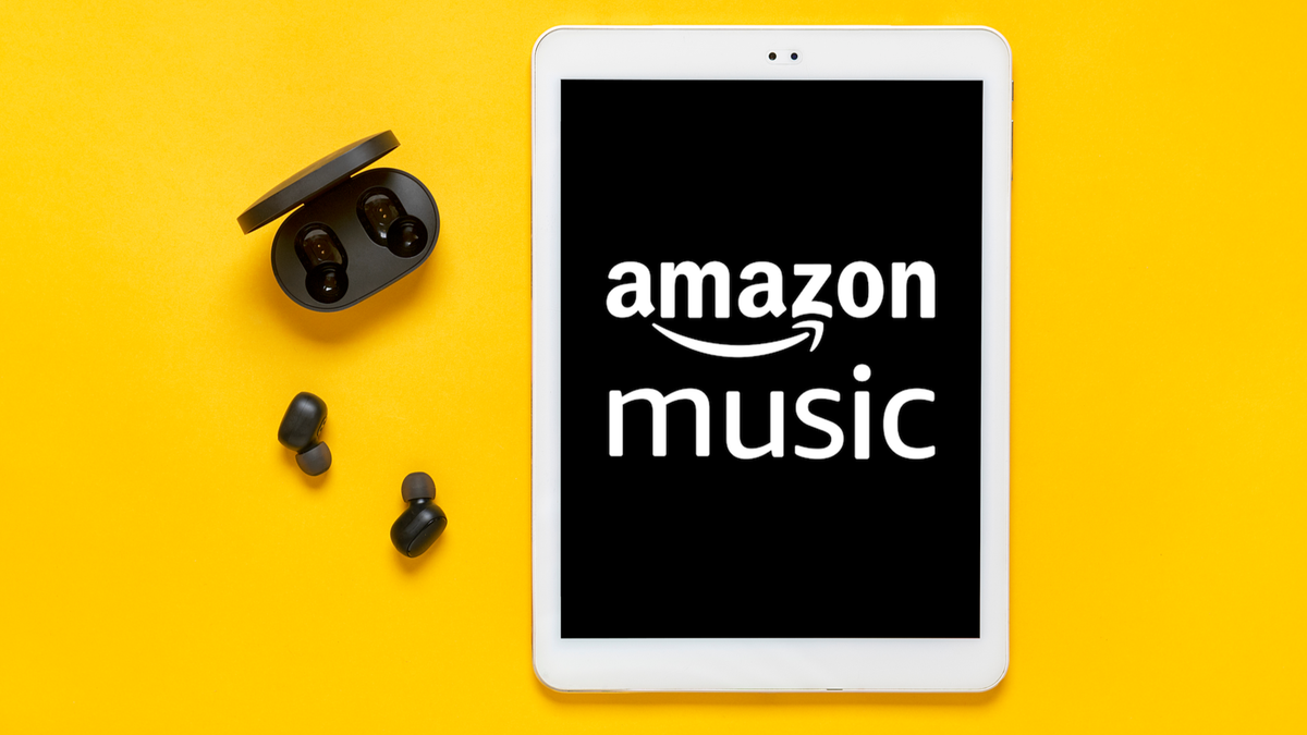 Amazon music logo on tablet next to earbuds and case against yellow background