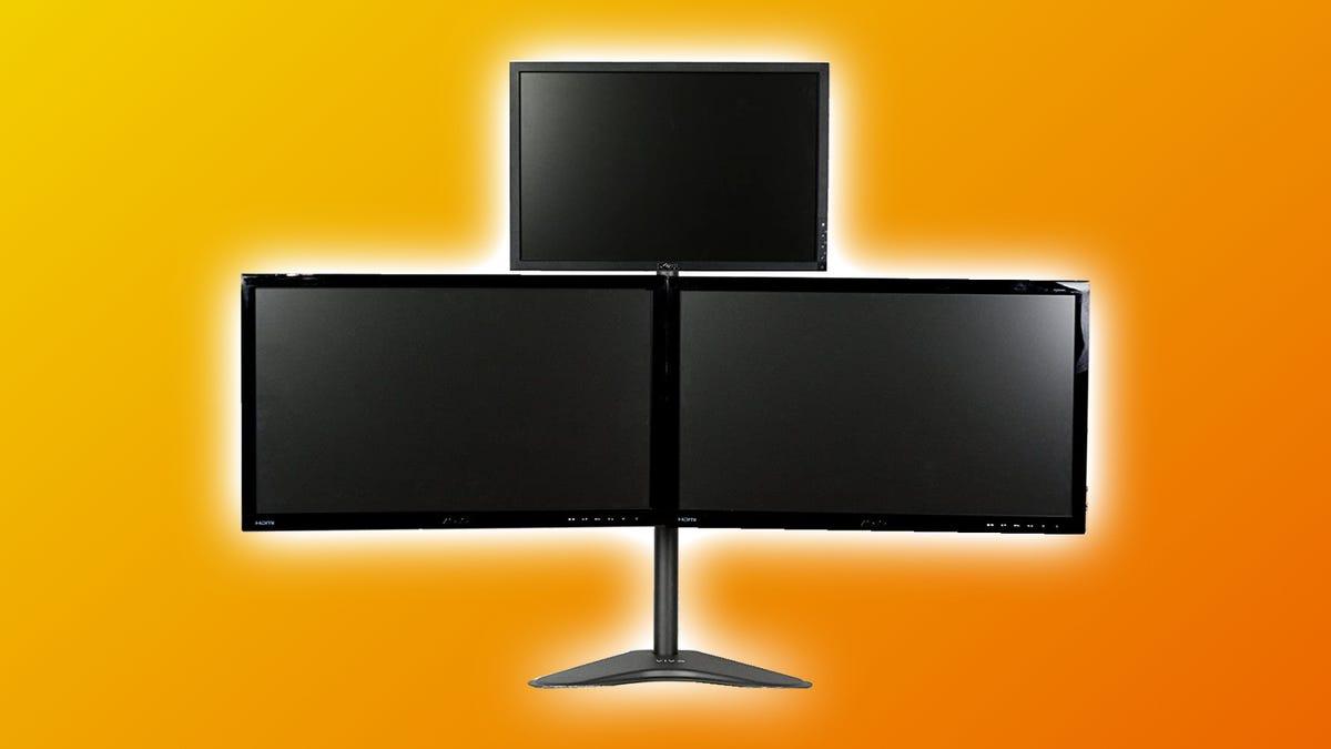 VIVO triple monitor freestanding mount against orange backdrop