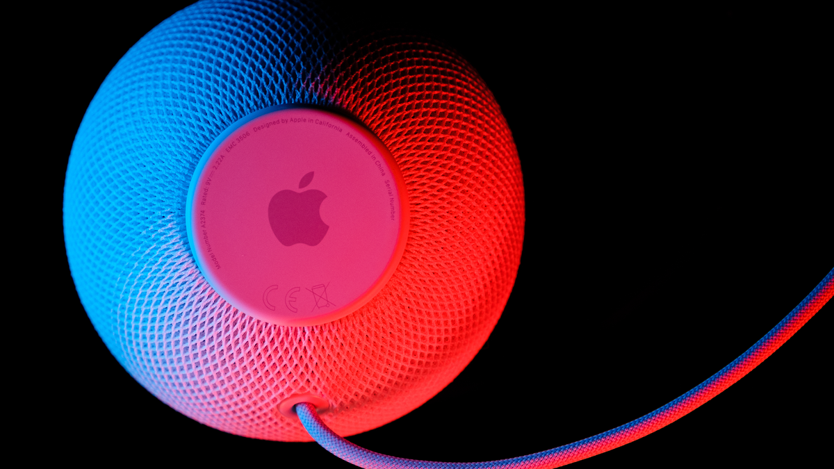 Apple HomePod mini smart speaker with Siri voice assistant in blue and red light