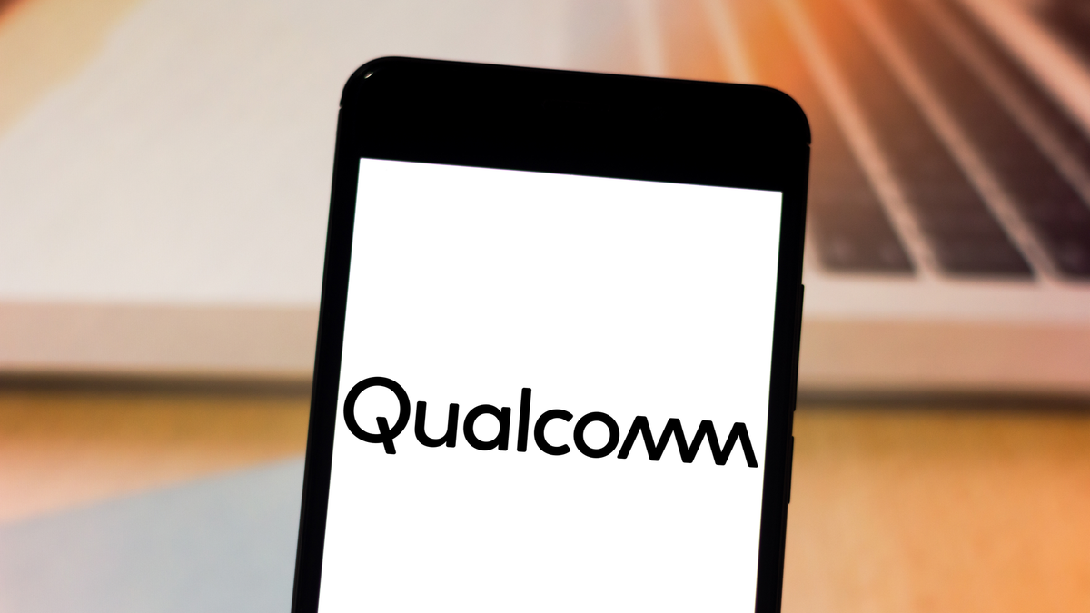 Qualcomm logo on a smartphone in front of a laptop