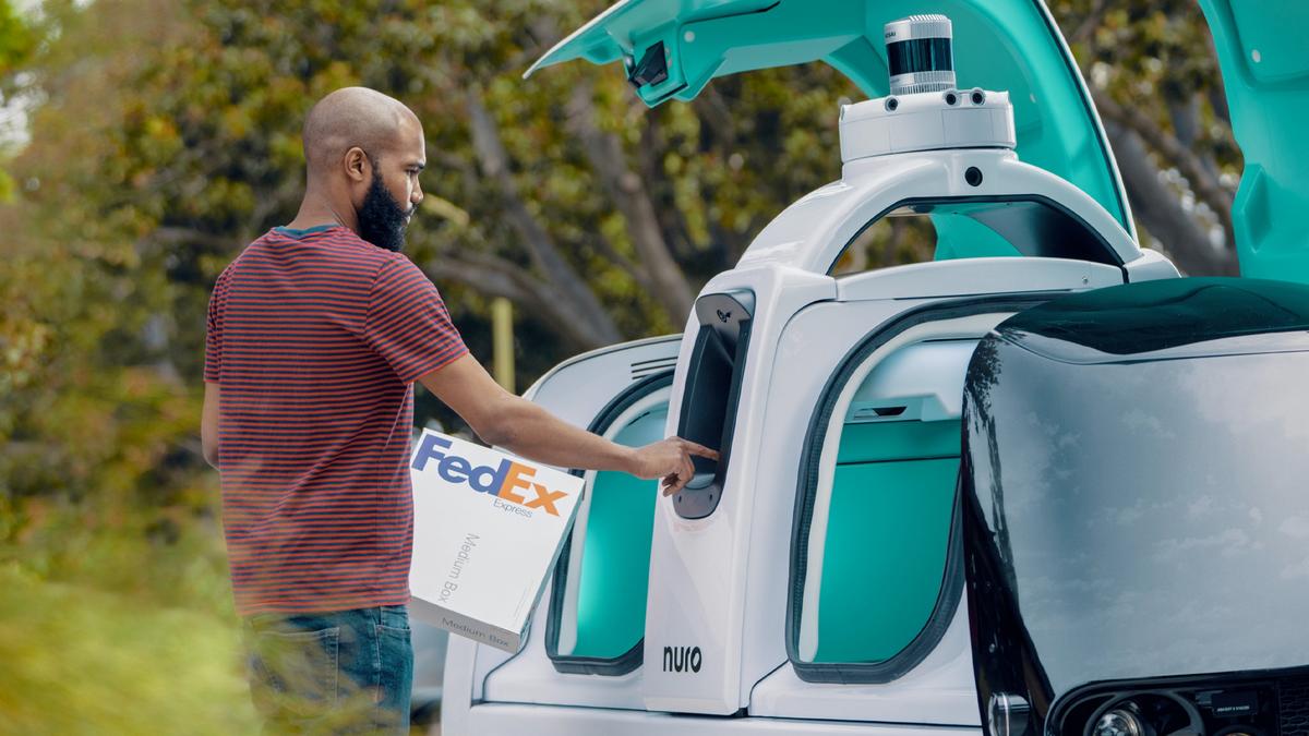 Una persona che prende il pacco FedEx da un veicolo di consegna autonomo.