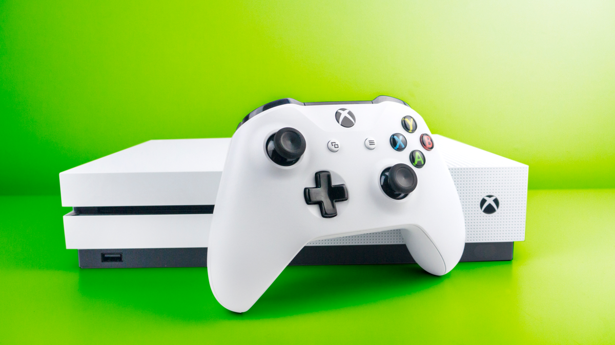 White Xbox One S console and matching controller in front of dynamically graduated green background