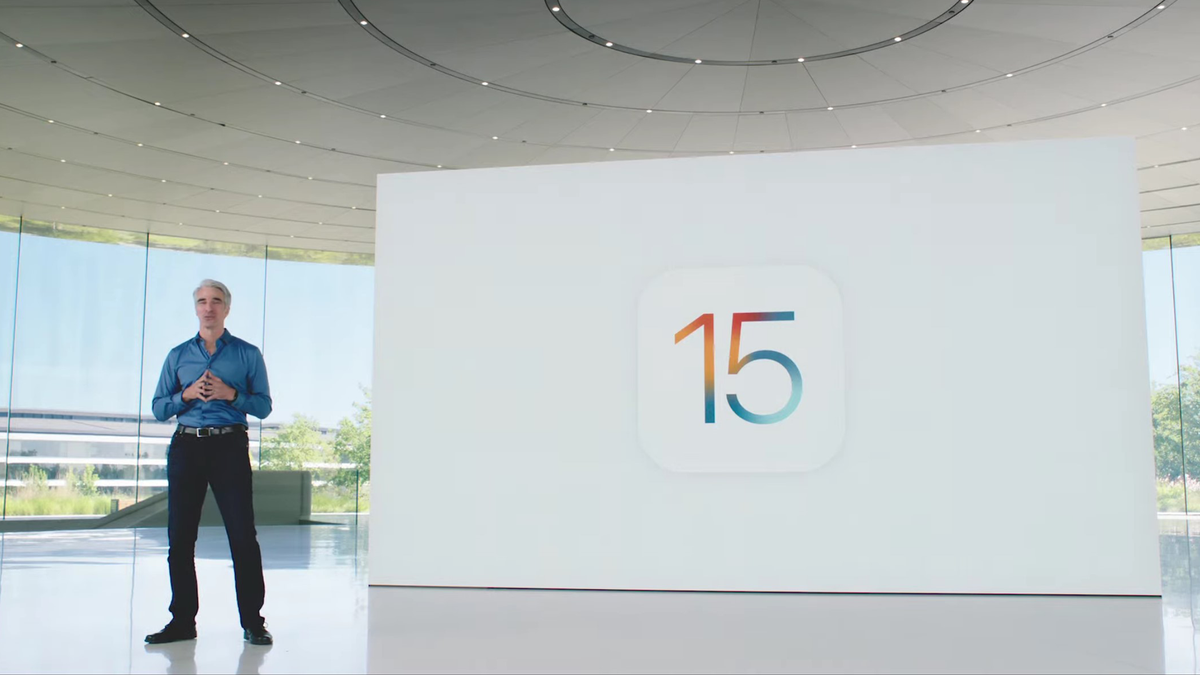 Tim Cook stands in Apple HQ next to iPadOS 15 sign