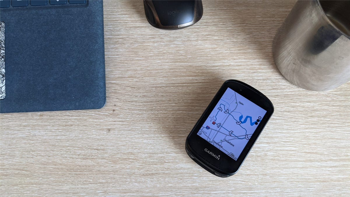 A Garmin Edge 530 on a desk next to a laptop, coffee cup, and mouse