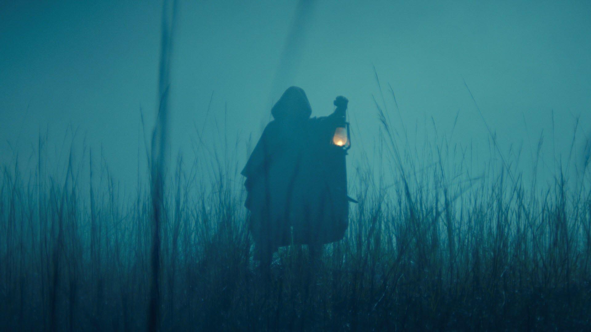 A figure hidden in shadow holding a lantern.