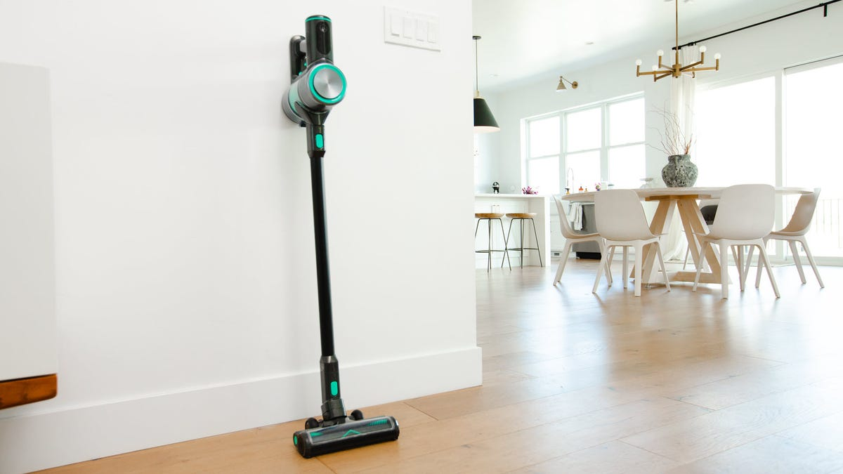 A stick vacuum cleaner mounted on the wall.