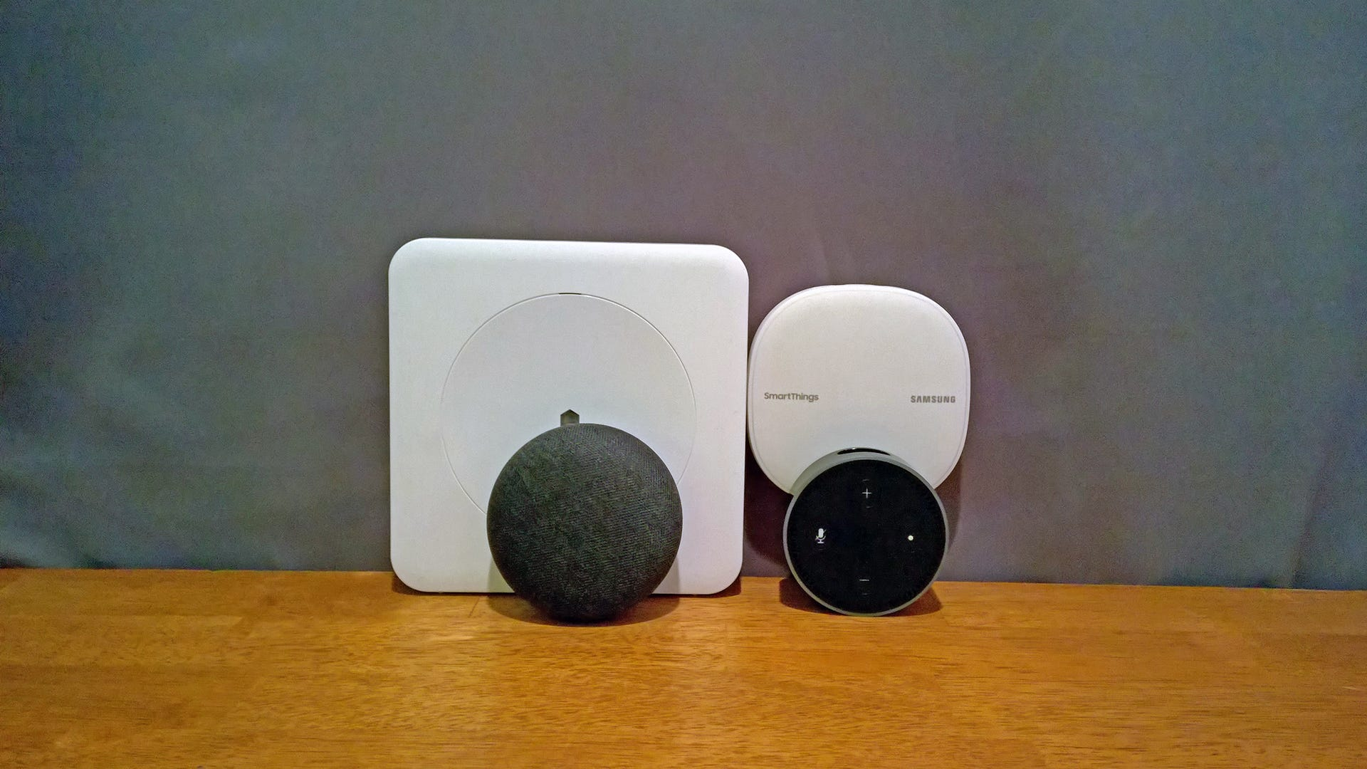 A Nest mini and Echo dot in front of a Wink and SmartThings hub
