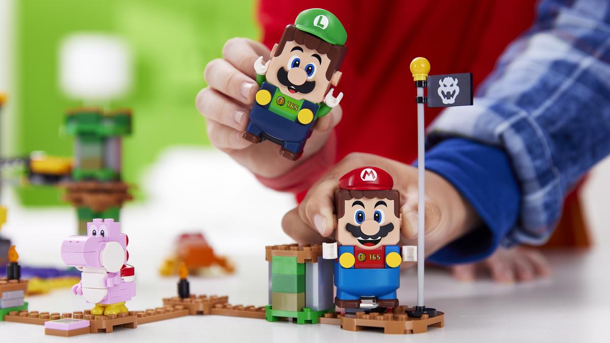 Two kids' hands holding Bluetooth LEGO Mario and LEGO Luigi