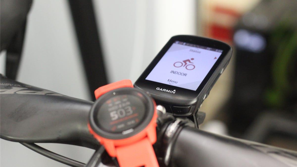 The Garmin Forerunner 745 in lava red and Garmin Edge 530 lying on a bike's handlebars