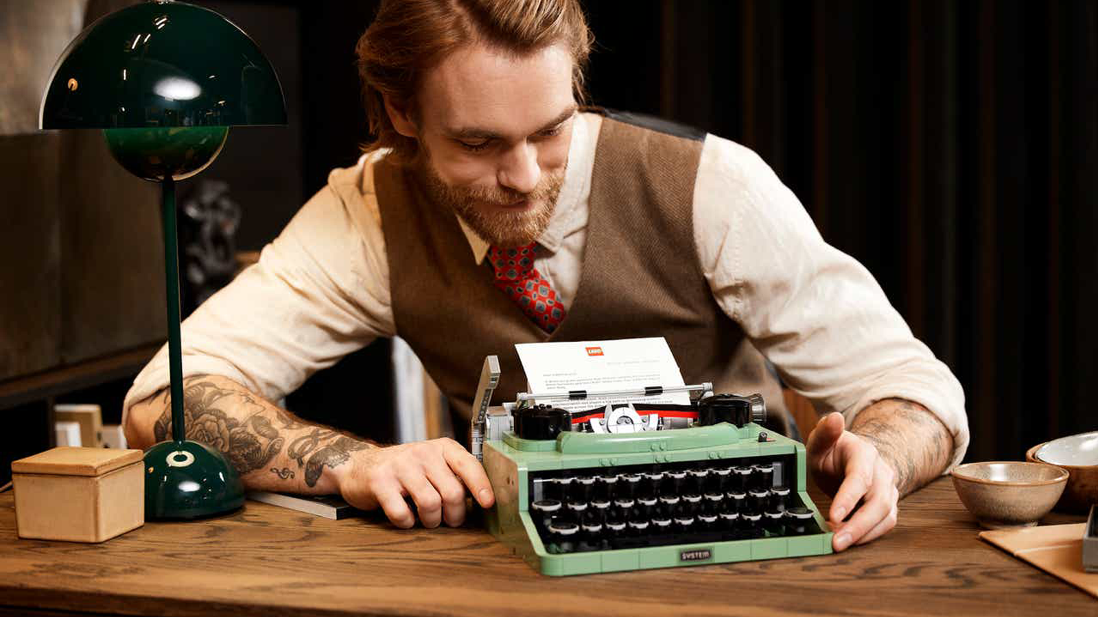 Person dressed in old-timey clothes sitting at wooden desk with LEGO Typewriter and other decorations