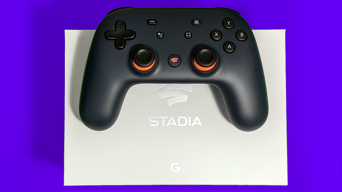 Closeup of a Google Stadia controller resting atop a white Stadia box against a bright purple background