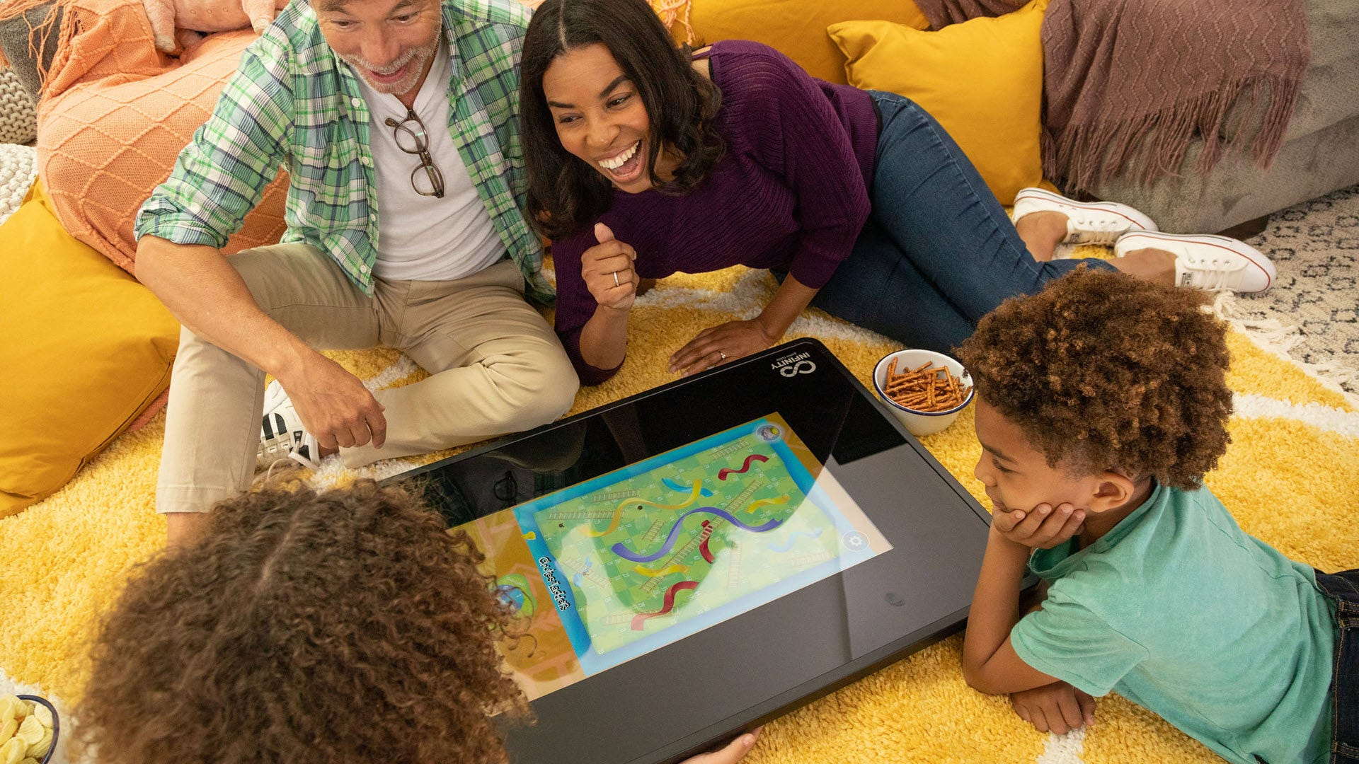 Four people playing a game of 'Chutes and Ladders' on the floor with a digital board game table.