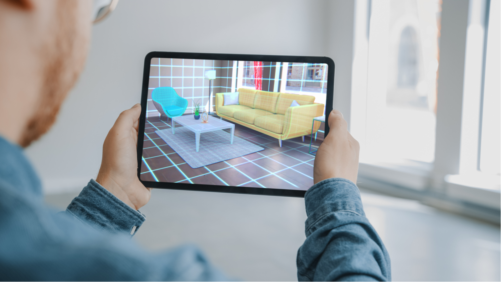 Person holding digital tablet with an augmented reality interior design app open while trying out furniture in the room virtually
