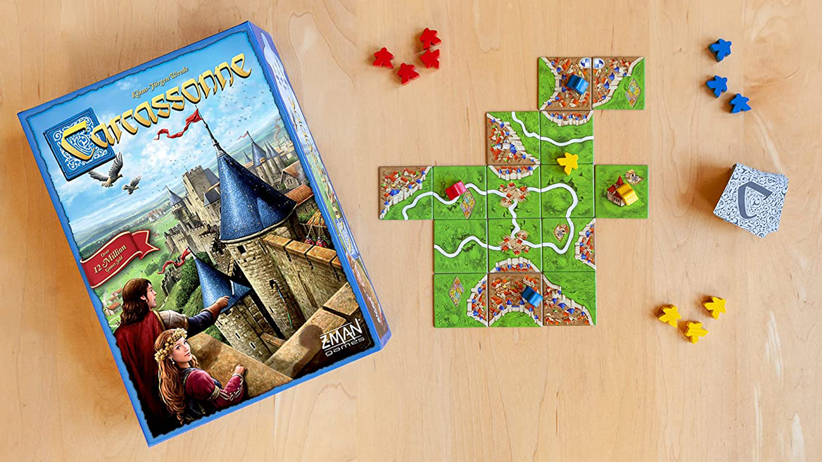 Carcassonne board game box on wooden table next to tiles and meeples