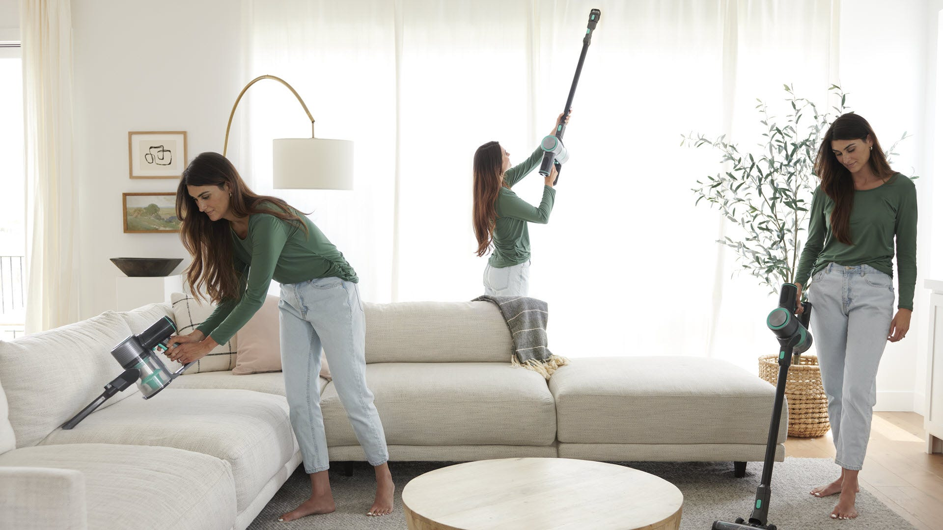 A woman vacuuming a living room using various brush and extension tools.