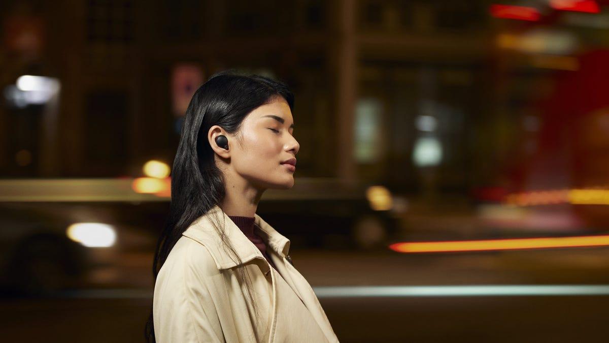 A woman wearing a set of true wireless earbuds