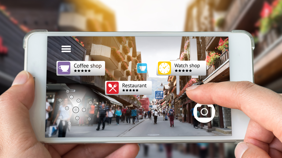 Person's hands holding smartphone using an augmented reality app to check information about nearby businesses while walking down a street