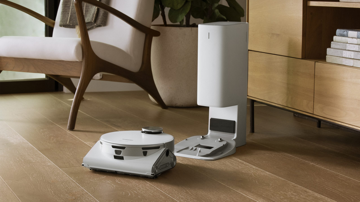The Jet Bot AI+ next to its Clean Station dock in a modern living room