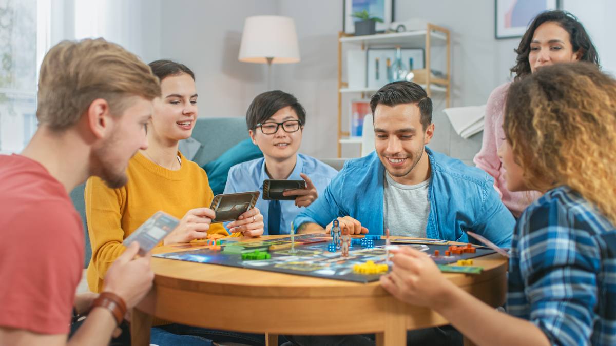 Diverse group of friends sitting around a table playing a board game
