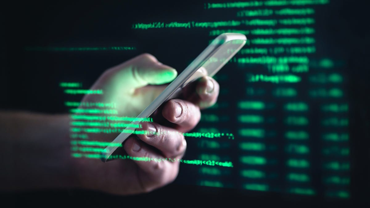 Hacker holding cellphone with code text overlay