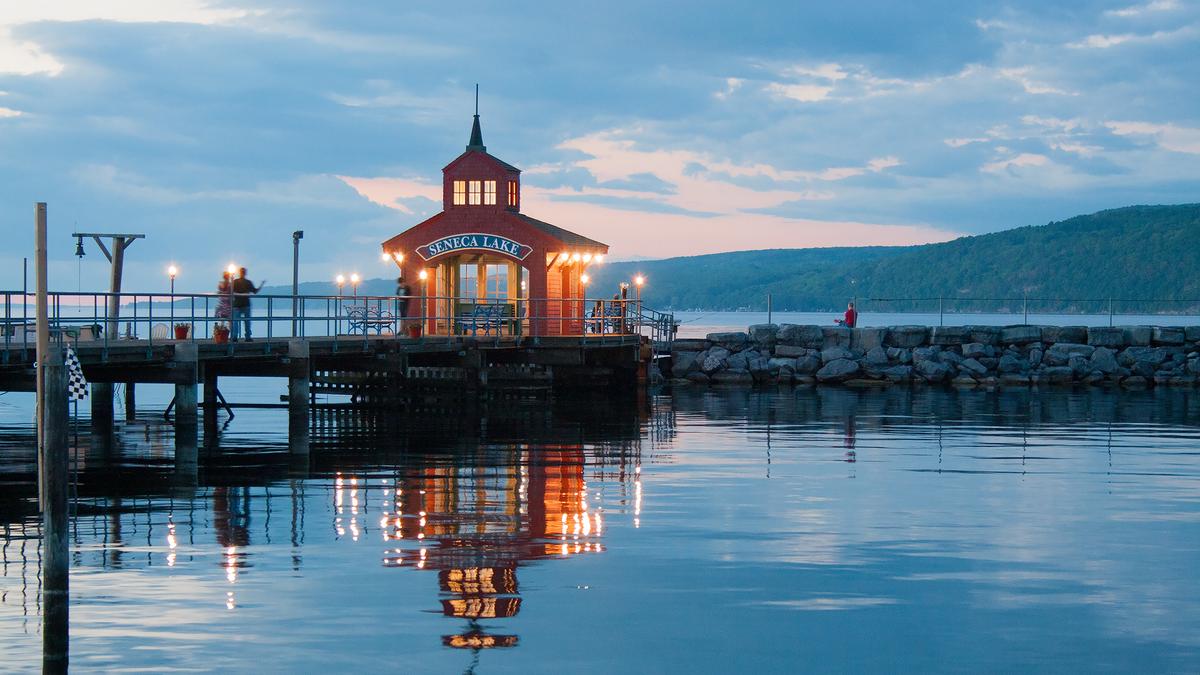 Pier on Seneca Lake with glowing lights at sunset