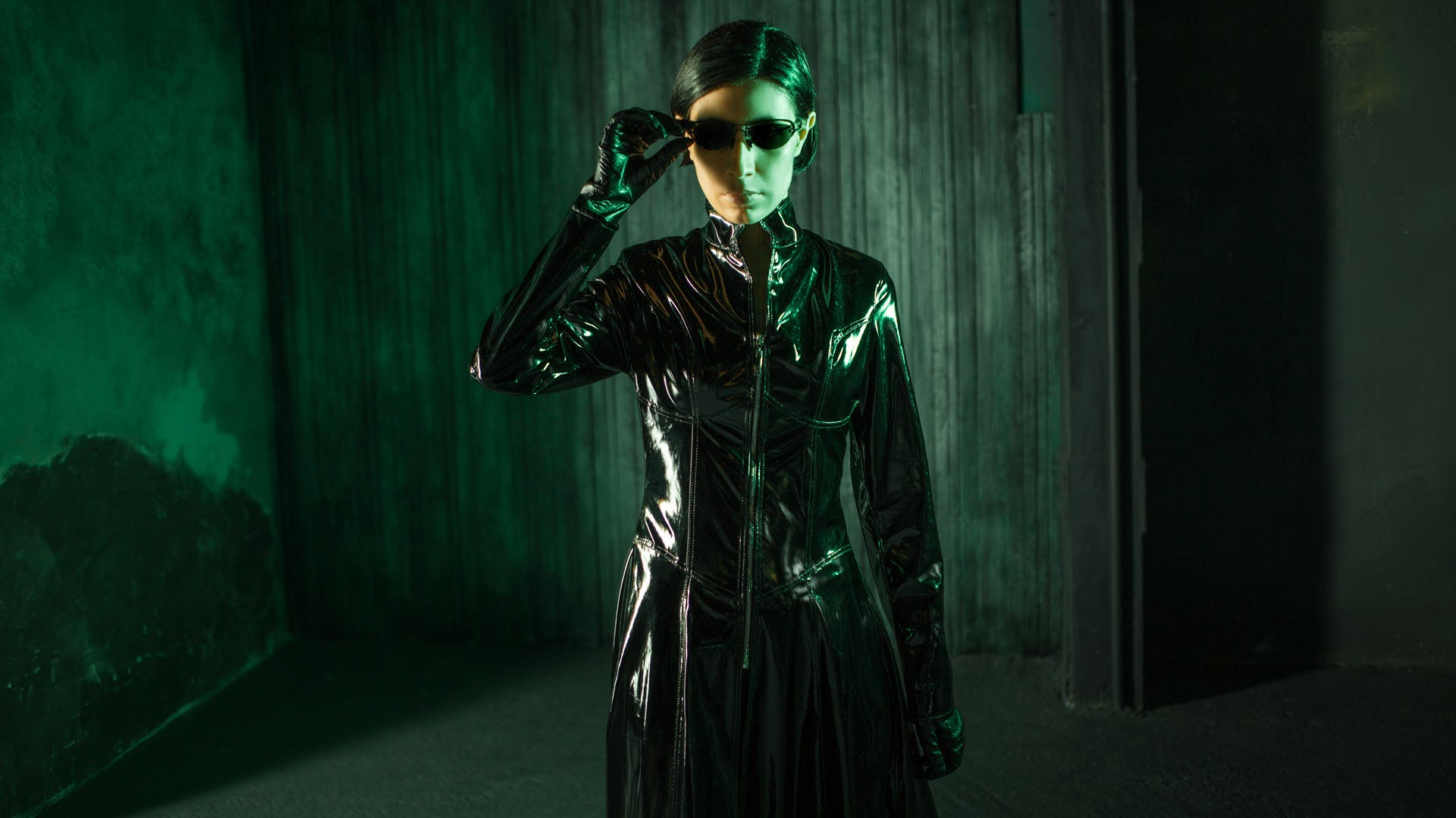 A young woman dressed like the character Trinity from 'The Matrix' surrounded by green hues.
