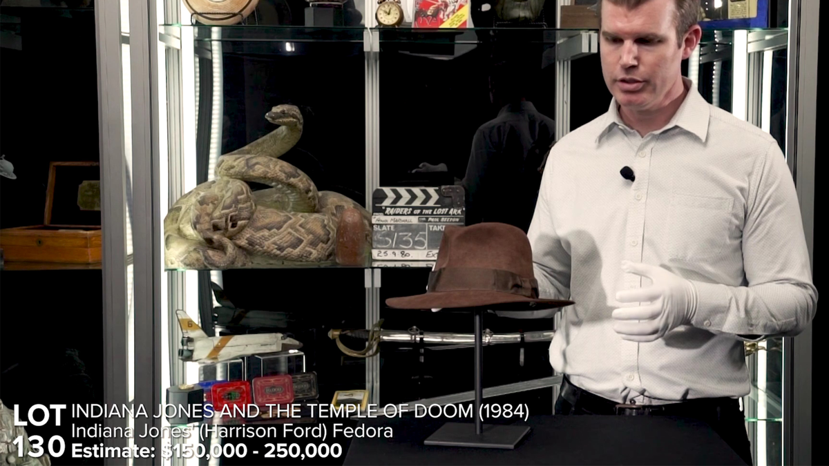 Still from auction house video with expert showing off the Indiana Jones fedora