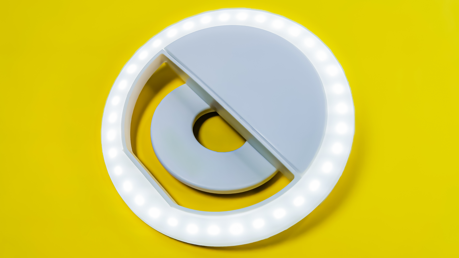 Close-up LED selfie circular ring light lamp for camera phone against bright yellow background
