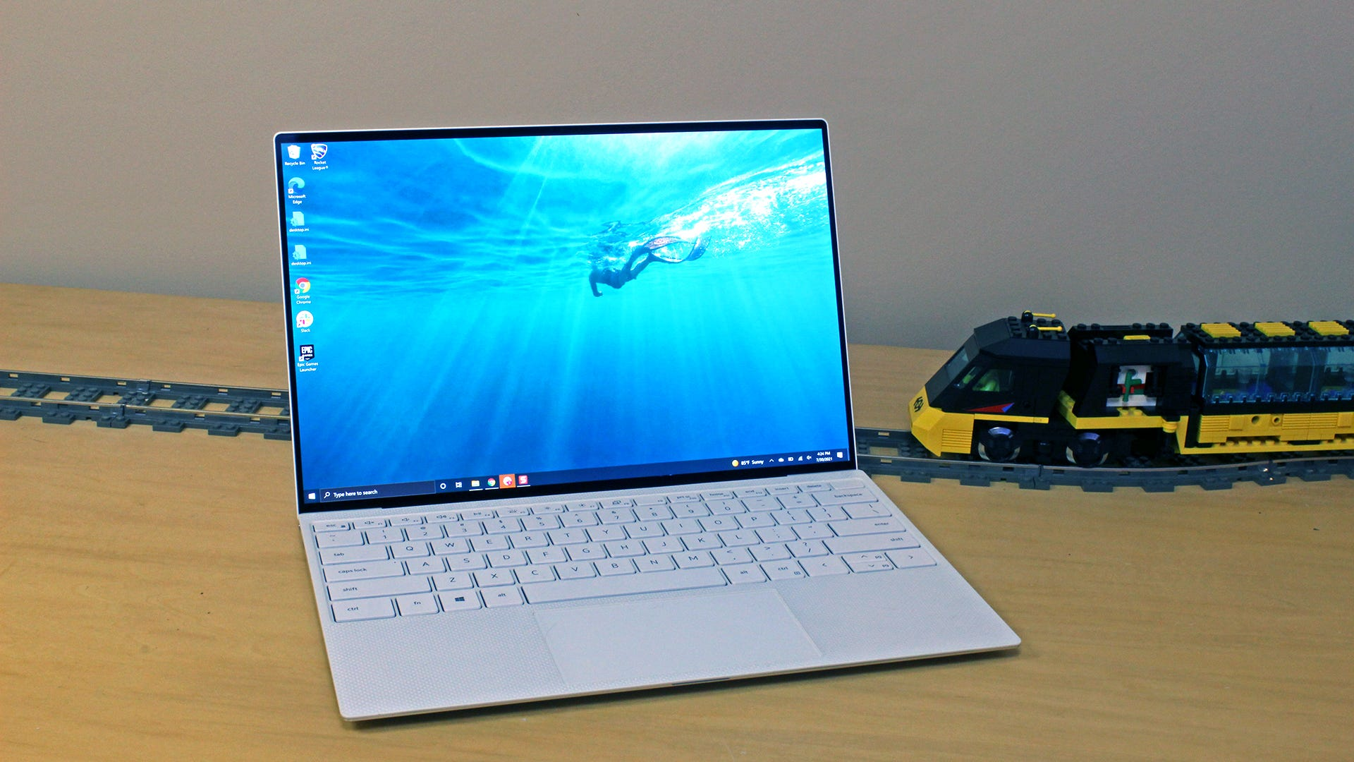 The XPS 13 OLED laptop sitting on a table with a toy train on a traintrack behind it.