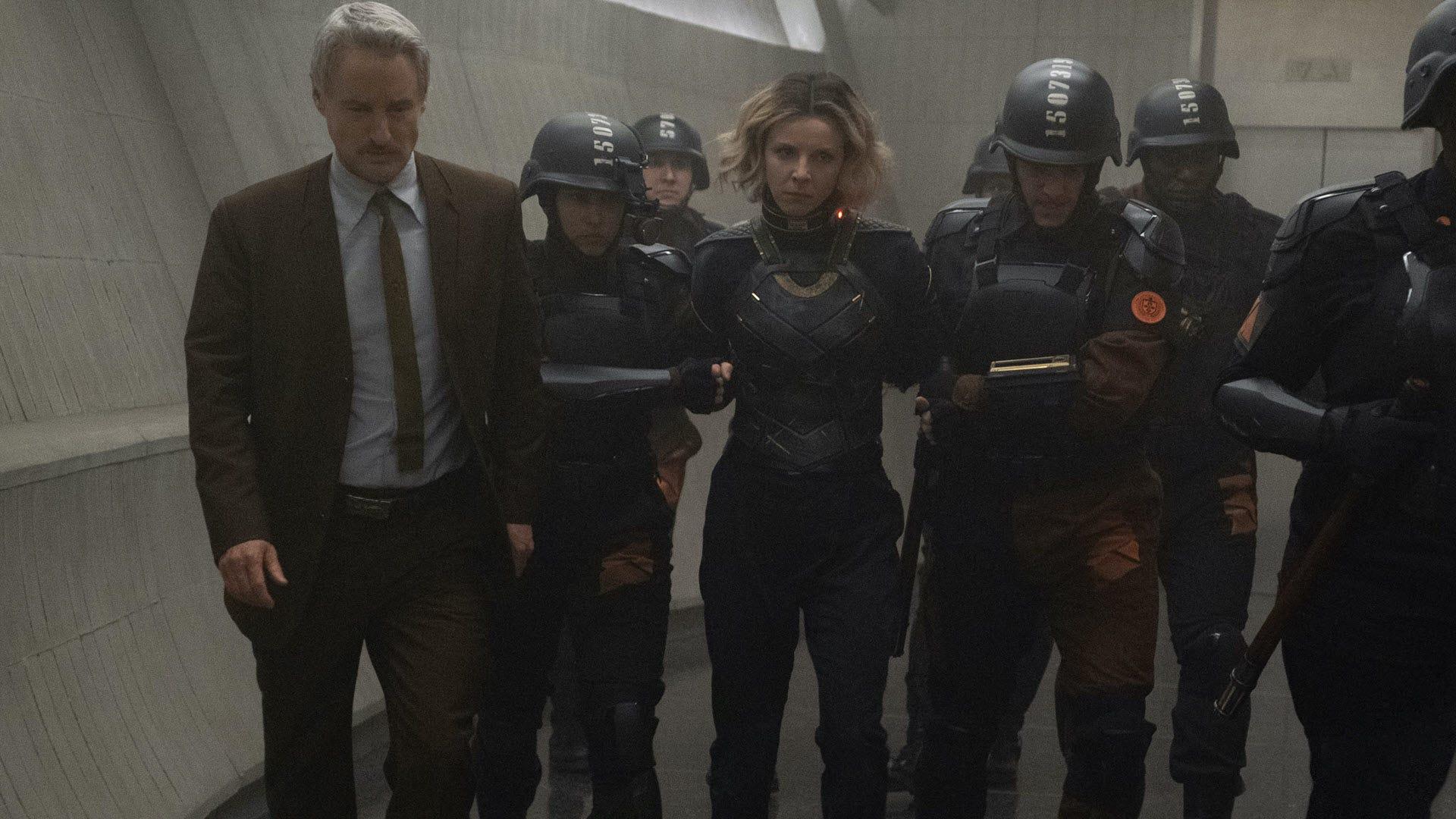 A captured Sylvie is led into a hallway.