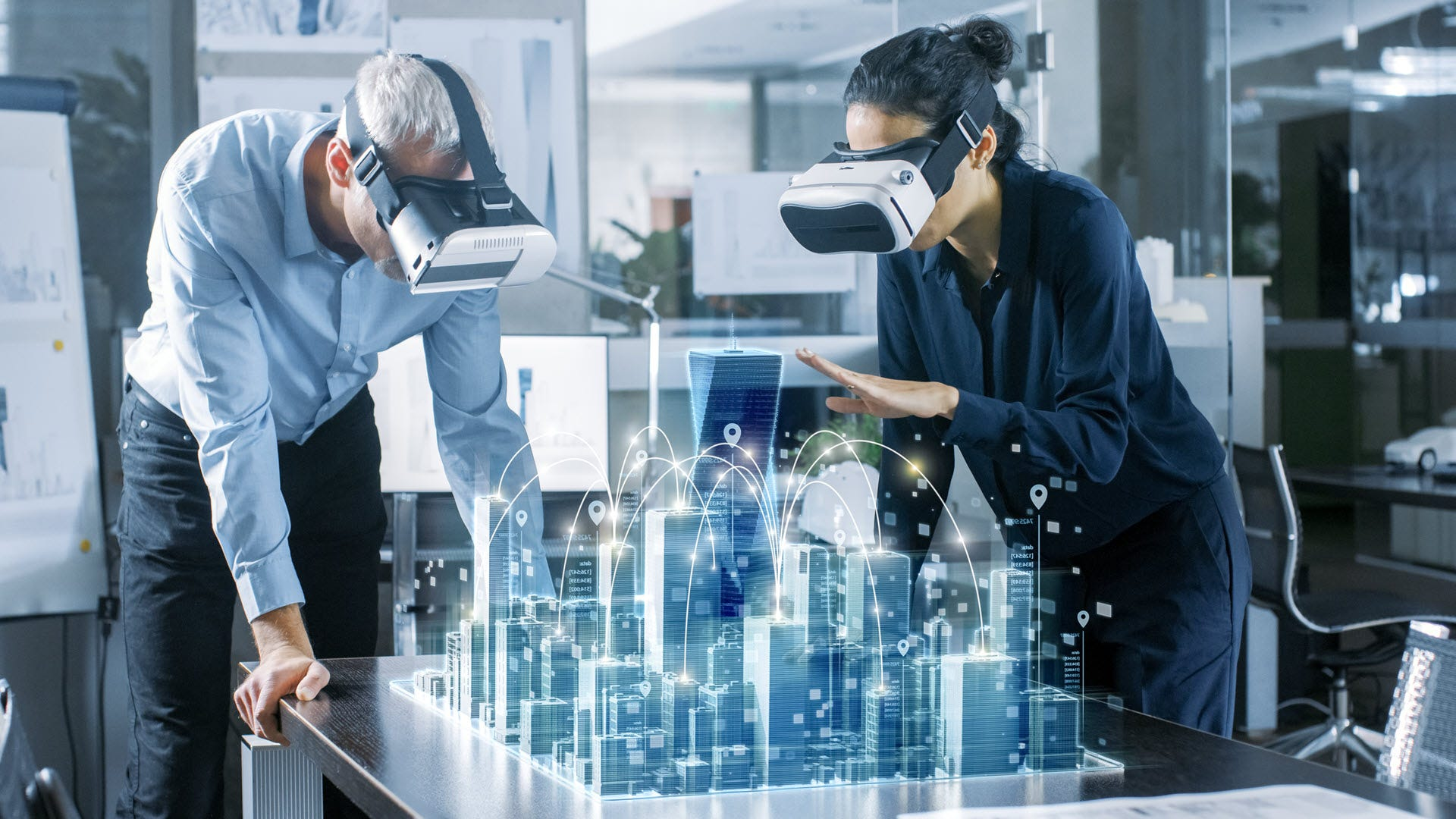 Two people in VR sets staring at an virtual architecture schematic of a city.
