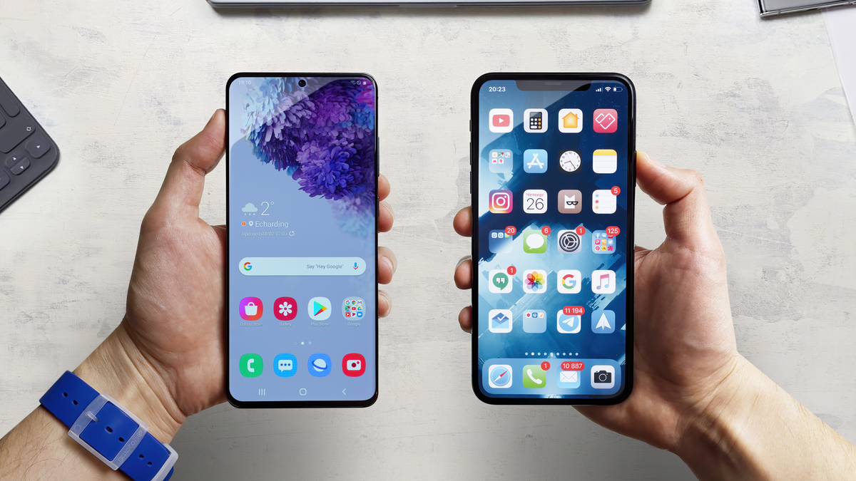An Android Samsung smartphone and an Apple iPhone next to each other with the displays turned on and unlocked