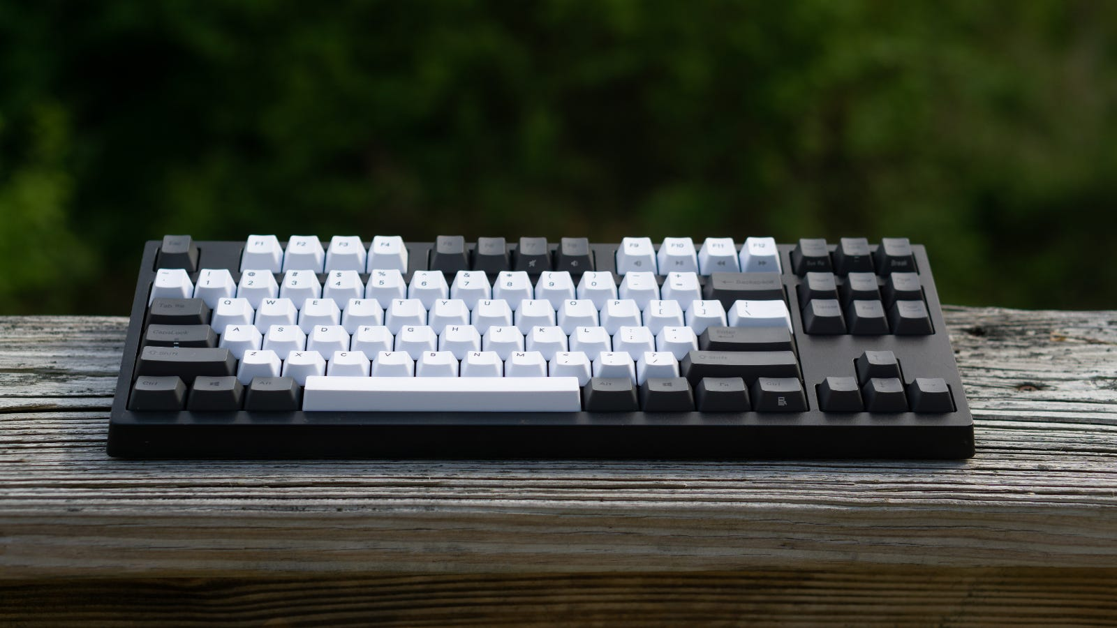 Gray, tenkeyless mechanical keyboard on a wooden railing