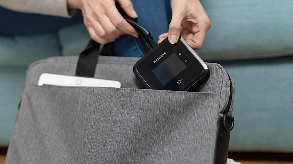 Person's hands placing the hotspot router into a modern laptop bag