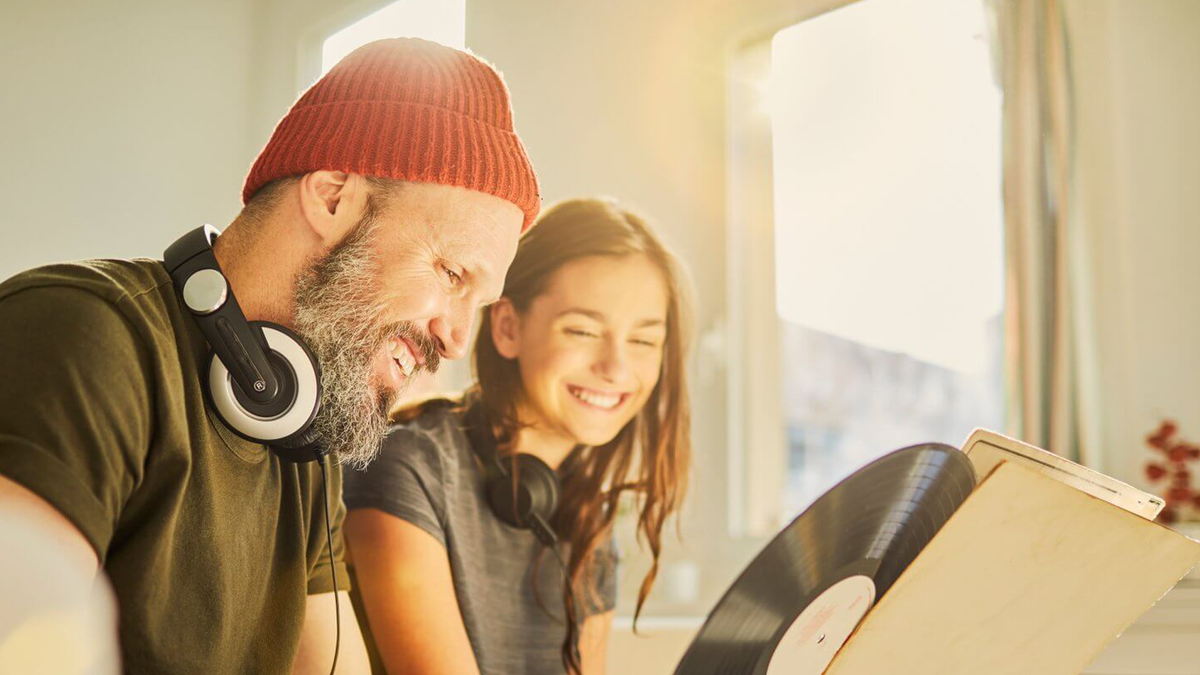 Two people wearing headphones listening to vinyl records and smiling in bright modern room