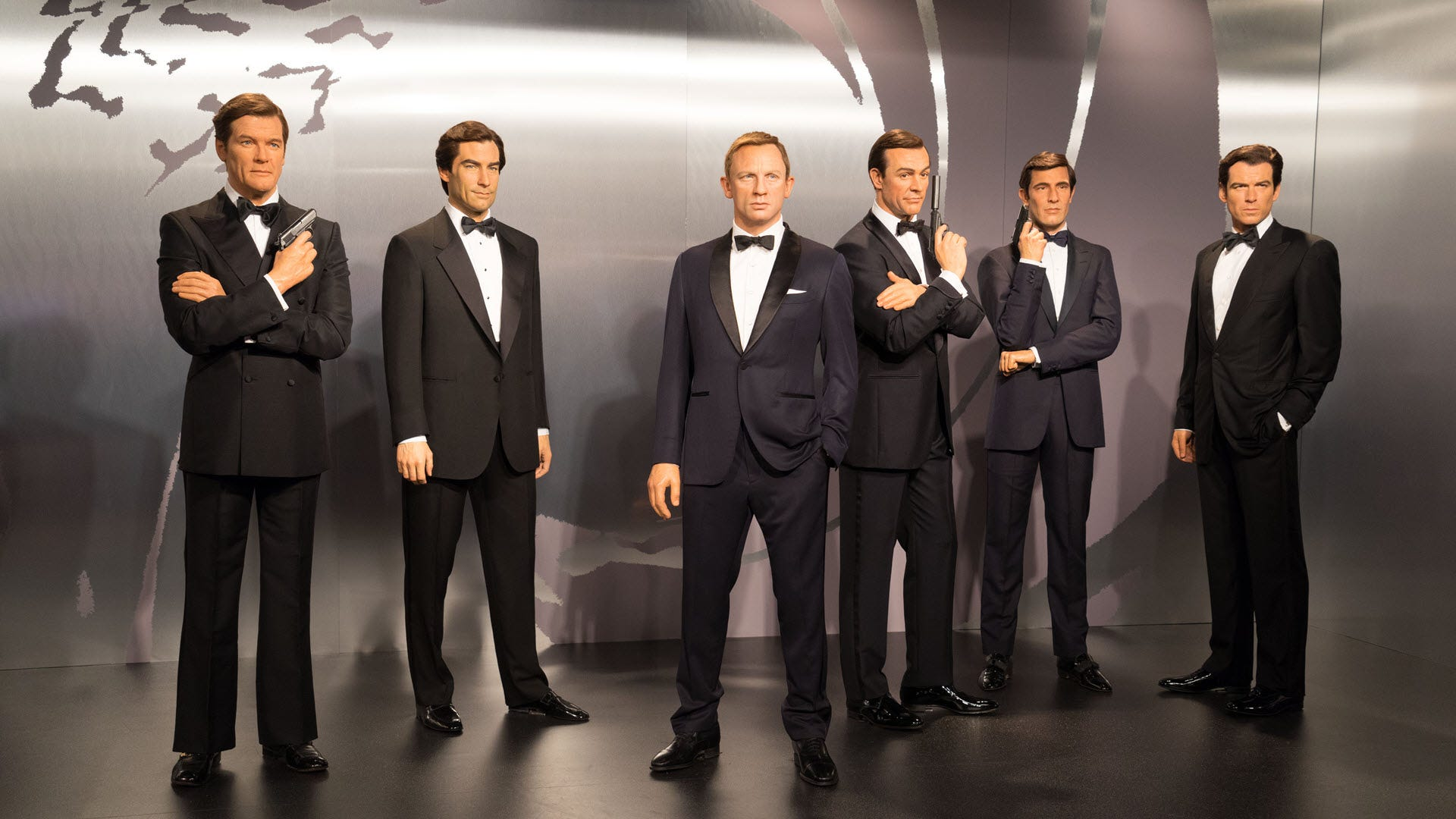 All the different versions of James Bond standing in front of a movie background.