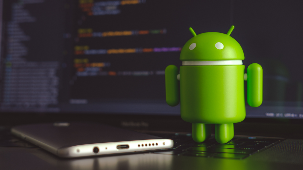 Google Android figure standing on laptop keyboard next to Android phone with code on screen in background
