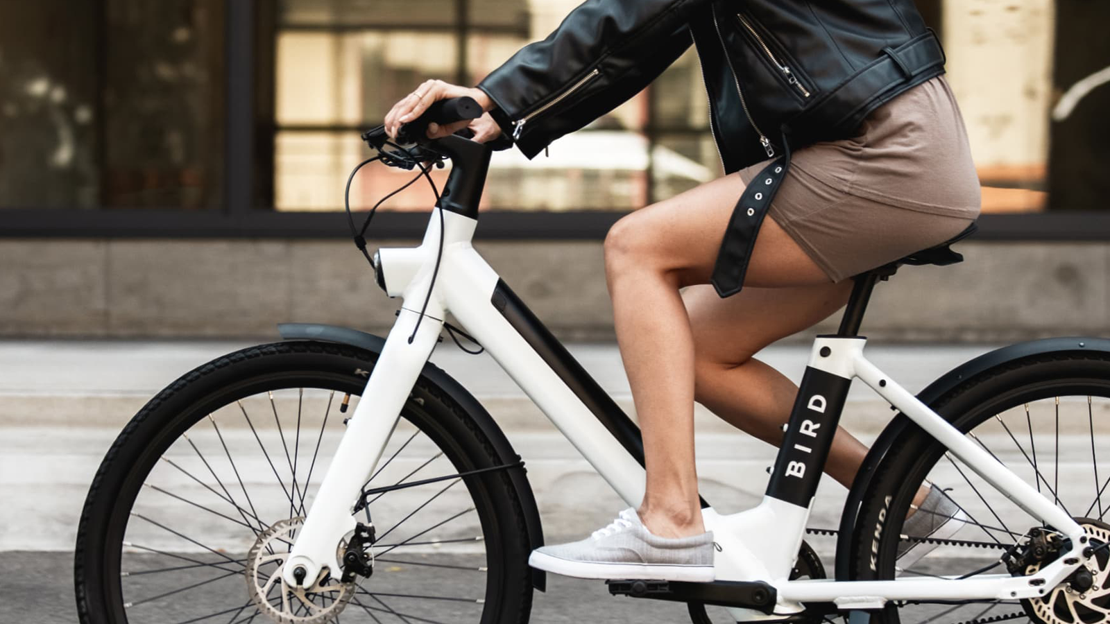 Person riding the Bird Bike on a modern urban street