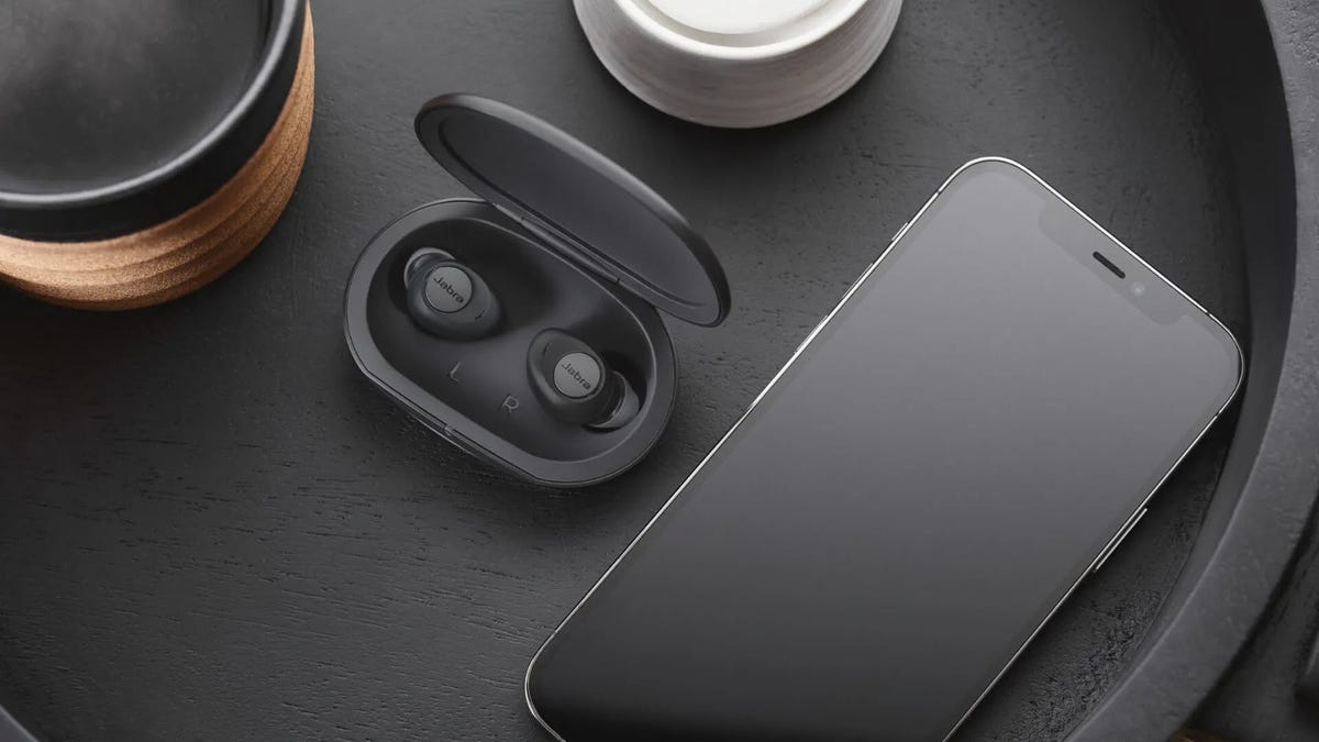 A pair of true wireless earbuds in a dark case next to a phone.