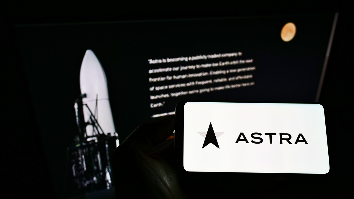 Person holding mobile phone with logo of American aerospace company Astra Space Inc. on screen in front of web page