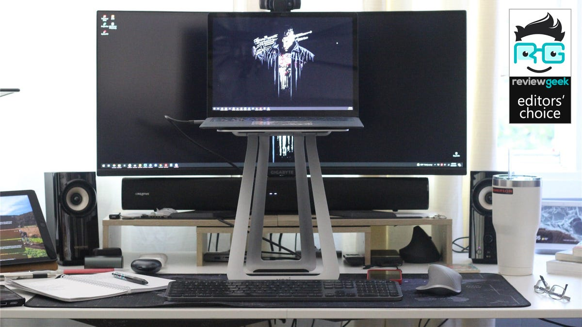 The VariDesk Portable Laptop Stand with a Surface Laptop 3 on it, sitting in front a big monitor