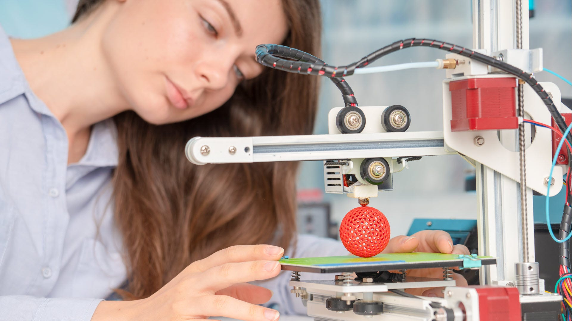 A woman looking at a 3D print in process.