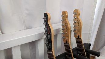 Indoor shot, a closeup of guitar headstocks in low light