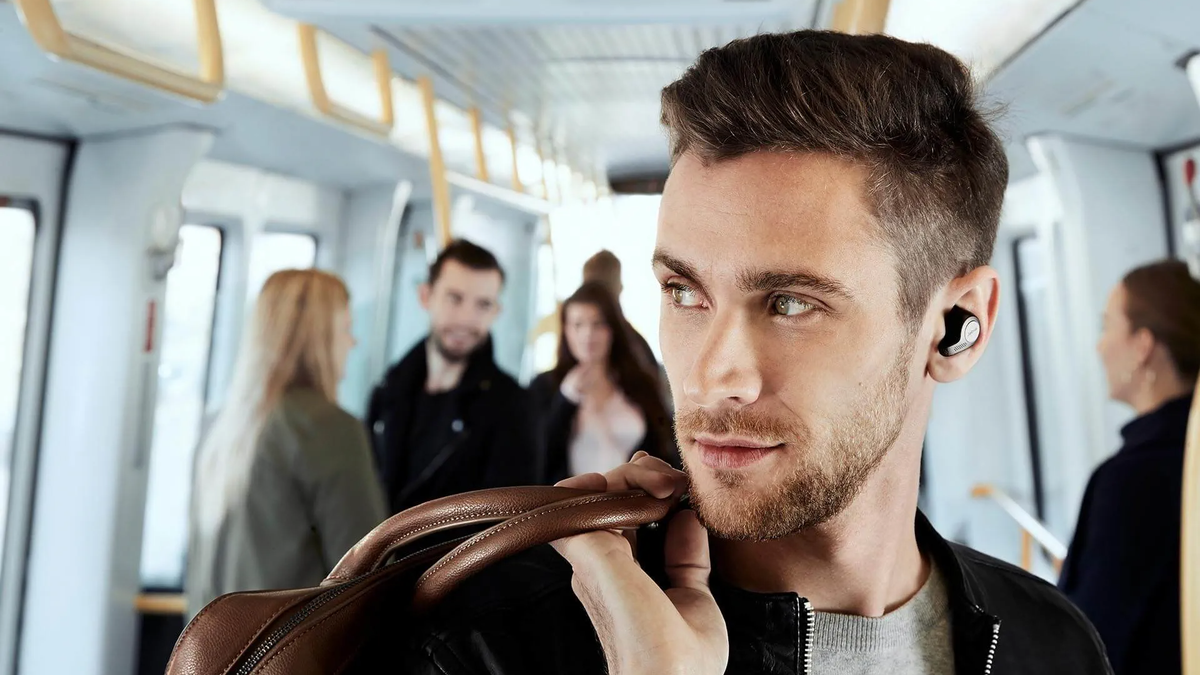 Person wearing Jabra Elite 65t earbuds while holding a bag on public transit