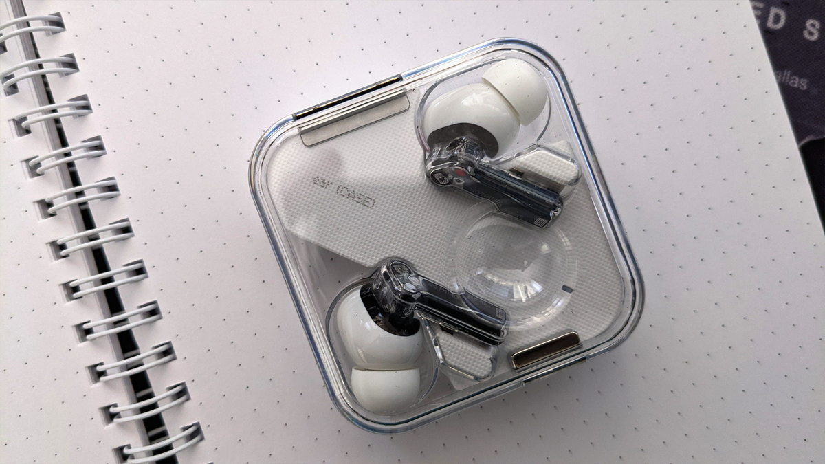 A photo of the Nothing Ear 1 earbuds on a white piece of paper. The paper shows through the Ear 1's transparent case.