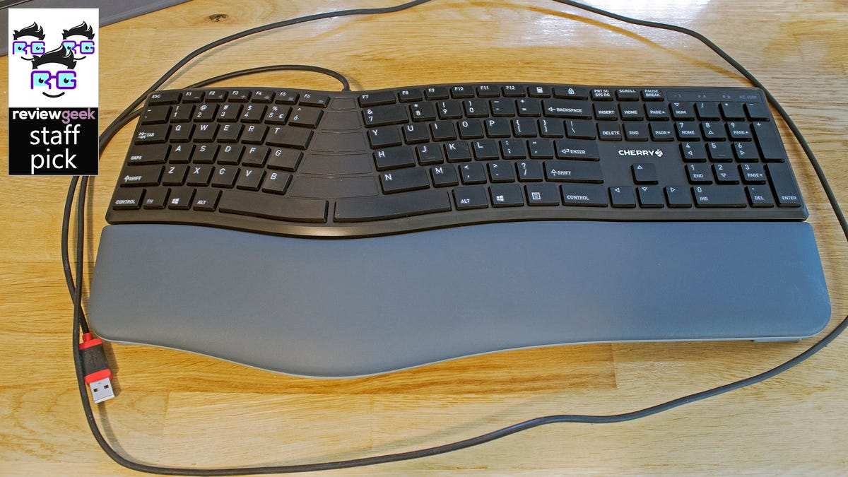 An ergonomic keyboard on a wood desk.