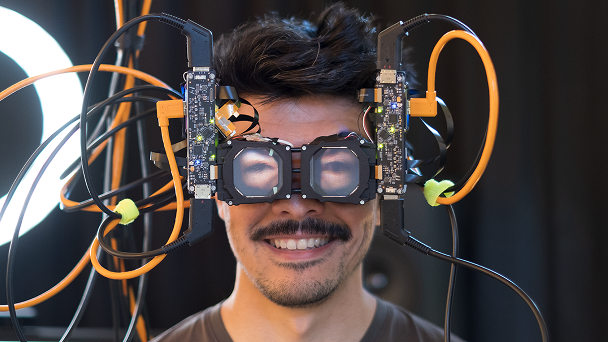 A man wearing a VR mask that shows his eyes using Reverse Passthrough tech.
